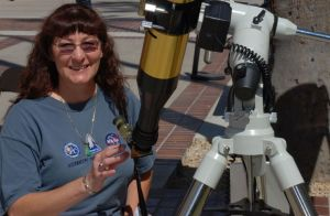 """Patricia Sullivan in NASA t-shirt with standing next to a telescope"""