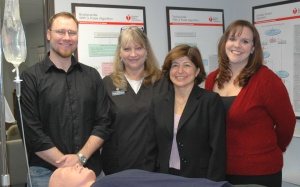 """Four people are smiling in front of a medical manikin"""